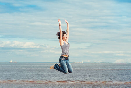 Happy young woman jumping on the beach outdoor photo