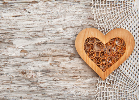 Wooden decorative heart on the lace fabric and old wooden background photo