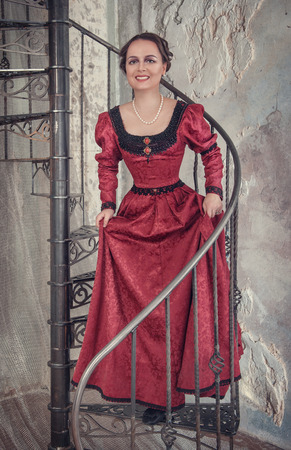 ruche: Beautiful young woman in red medieval dress on the stairway Stock Photo