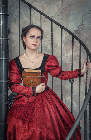 Beautiful young woman in red medieval dress with book on the stairway photo
