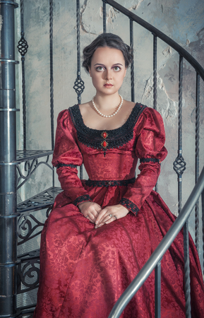 Beautiful young woman in red medieval dress on the stairway Stock Photo