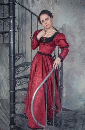 middeleeuwse jurk: Mooie jonge vrouw in rode middeleeuwse kleding op de trap