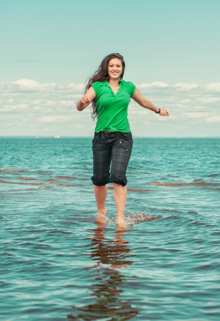 Happy beautiful woman running on the water of sea photo