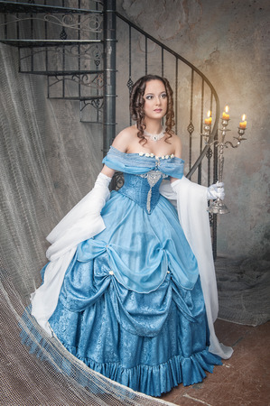 ruche: Beautiful young  woman in long blue medieval dress with candelabrum