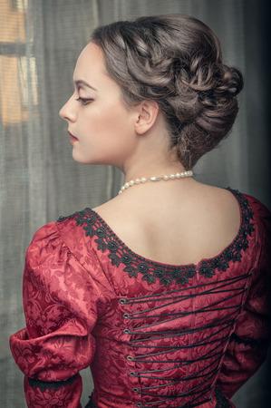 historische: Portret van jonge mooie middeleeuwse vrouw in rode jurk