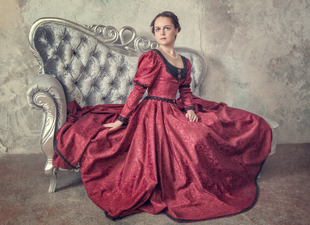 Beautiful young woman in red medieval dress on the sofa