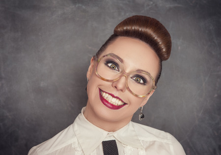Crazy smiling woman in the eyeglasses on the blackboard background