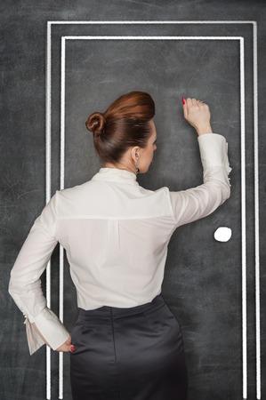 Stijlvolle zakelijke vrouw in de witte blouse klop op tekening deur