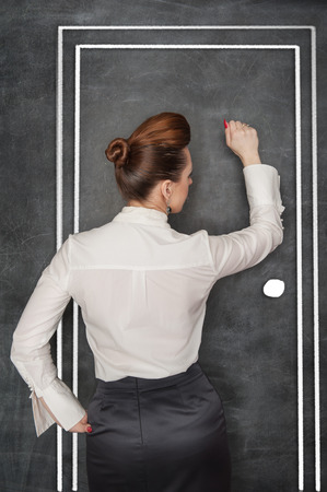 woman handle success: Stylish business woman in the white blouse knock on drawing door Stock Photo