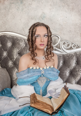 Beautiful young woman in blue medieval dress with book on the sofa photo