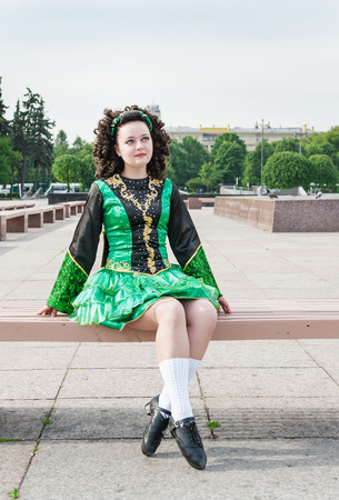 Young woman in irish dance dress and wig sitting on the bench outdoor photo