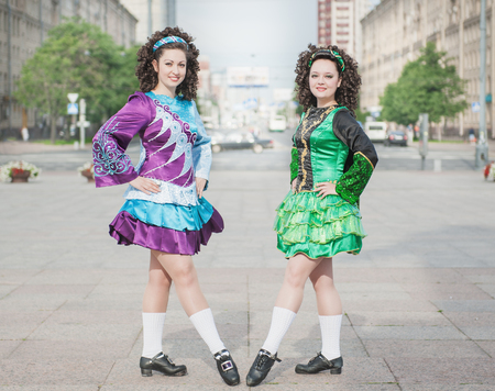 Two women in irish dance dresses and wig posing outdoor photo