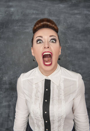 Angry screaming woman on the blackboard background