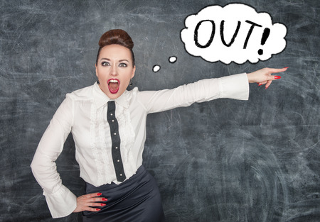Angry screaming teacher in white blouse pointing out