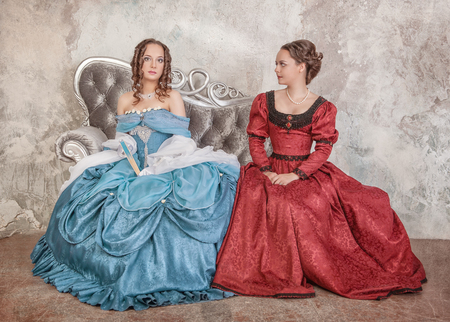 Two beautiful young women in blue and red medieval dresses on the sofa photo