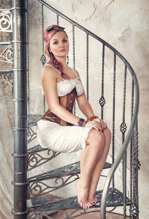 Beautiful steampunk woman with pink hair and trousers on the stairway photo