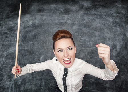 Angry screaming teacher with pointer in her hand