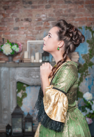Praying young beautiful woman in green medieval dress photo