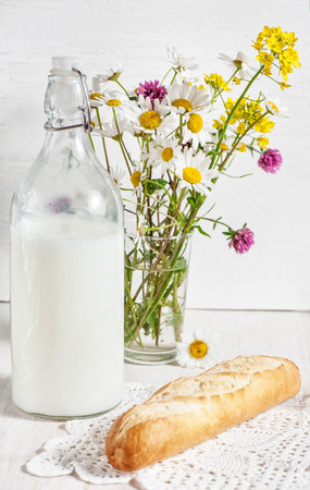 Fresh milk in old fashioned bottle with baguette and flowers on the old wooden background photo