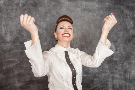 Happy smiling business woman with her arms in the air photo
