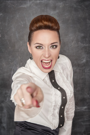Angry screaming teacher in white blouse pointing out photo
