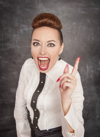 Angry screaming teacher in white blouse threaten by finger photo