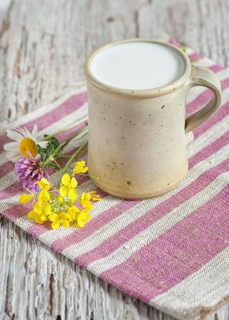 Fresh milk in ceramic mug and flowers bouquet on the napkin photo