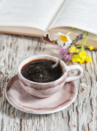 Cup of coffee and flowers in open book on the wooden table  photo