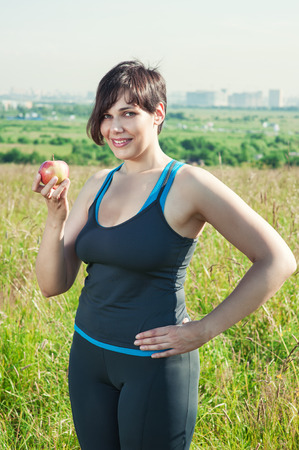 Fitness beautiful plus size woman with apple outdoor photo