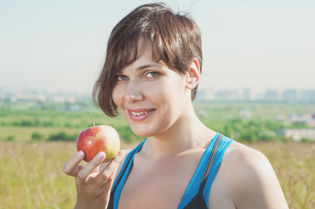Beautiful brunette fitness woman with apple outdoor photo