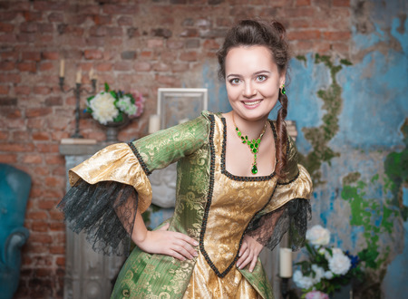 Beautiful young  woman in medieval dress in the room photo