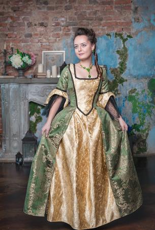 middeleeuwse jurk: Mooie jonge vrouw in lange middeleeuwse kleding in de kamer