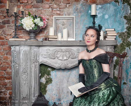 ruche: Beautiful young  woman in long medieval dress sitting near fireplace Stock Photo