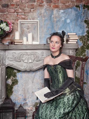 Beautiful young  woman in long medieval dress sitting near fireplace photo