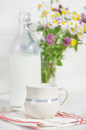 Fresh milk in ceramic mug, old fashioned bottle and wildflowers photo