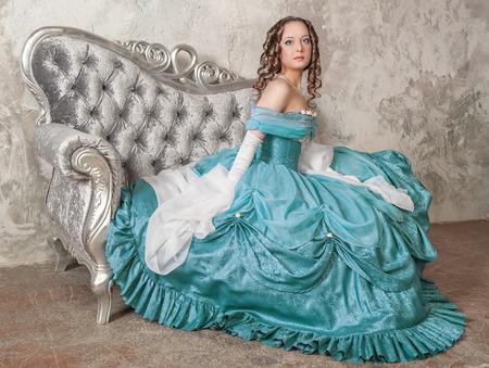 Joven y bella mujer en traje medieval azul en el sofá