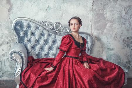 medieval dress: Joven y bella mujer en traje medieval rojo en el sof� Foto de archivo