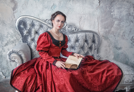 ruche: Beautiful young woman in red medieval dress on the sofa with book Stock Photo