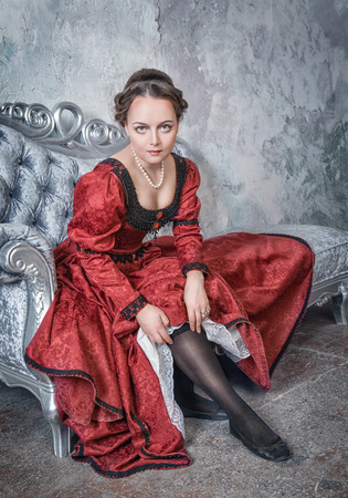 Beautiful woman in red medieval dress putting stockings on the sofa photo