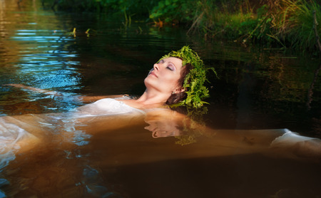 Young beautiful drowned woman with fern wreath lying in the water photo