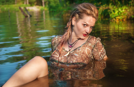 Beautiful young woman lying in the water outdoor