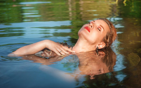 Beautiful young woman lying in the water outdoor photo