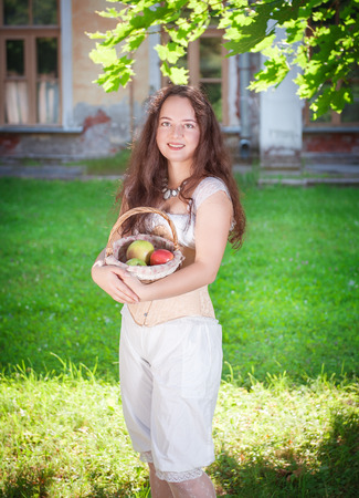 Beautiful young woman in corset and trousers holding basket with apples outdoor photo