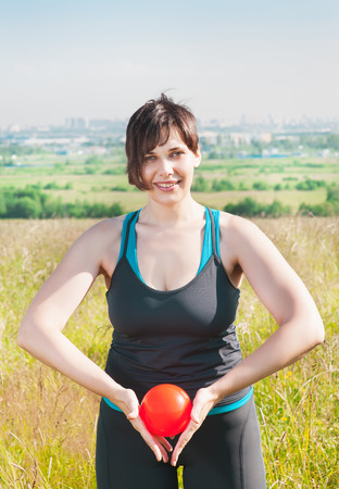 Beautiful plus size woman exercising with small ball outdoor photo