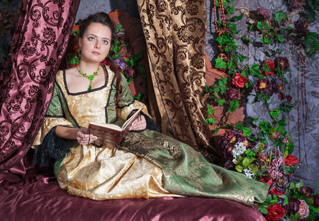 middeleeuwse jurk: Mooie jonge vrouw in middeleeuwse kleding leesboek groen