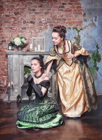 Beautiful young woman in long medieval dress consoling her friend photo