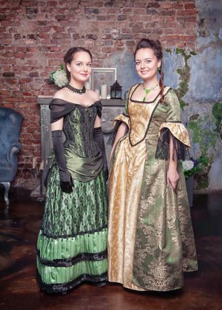 Two young beautiful women in long medieval dresses  photo