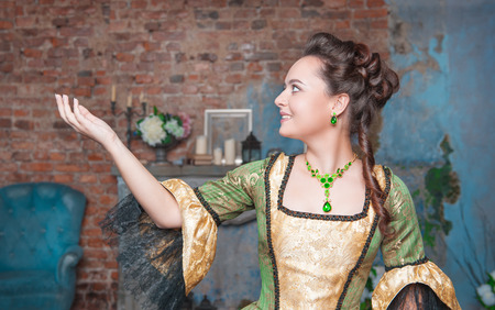 ruche: Beautiful young  woman in green medieval dress stretching hand to something Stock Photo