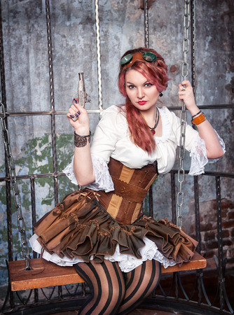 Beautiful steampunk woman with pink hair with gun in the metal cage photo
