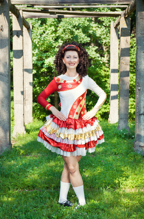 Young woman in irish dance dress and wig posing outdoor photo
